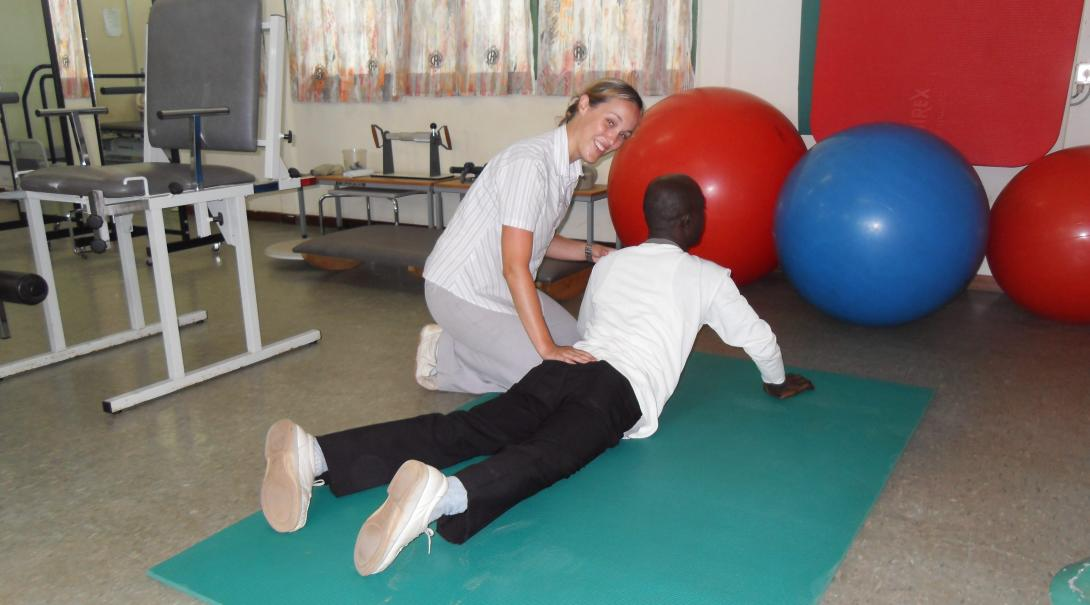 A Projects Abroad volunteer doing a physiotherapy internship in Ghana helps an adult with his therapy routine.